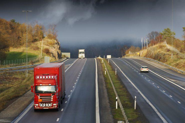 Rød lastbil med orange fareskilt og ADR stykgods